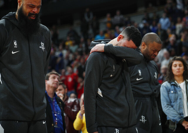 From left to right, Houston Rockets center Tyson Chandler, guard Austin Rivers and forward P.J. Tucker react during a tribute to Kobe Bryant before an NBA basketball game against the Denver Nuggets, Sunday, Jan. 26, 2020, in Denver. Bryant died in a California helicopter crash Sunday. (AP Photo/David Zalubowski)