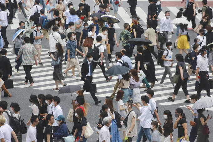 People wearing face masks to protect against the spread of the coronavirus cross a street in Tokyo, Wednesday, July 28, 2021. Tokyo Gov. Yuriko Koike on Wednesday urged younger people to cooperate with measures to bring down the high number of infections and get vaccinated, saying their activities are key to slowing the surge during the Olympics. (AP Photo/Koji Sasahara)