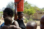 A woman heads home after fetching water at a borehole in Harare, Tuesday, Sept, 24, 2019.The more than 2 million residents of Zimbabwes capital and surrounding towns are now without water after authorities shut down the citys main treatment plant, raising new fears about disease after a recent cholera outbreak while the economy crumbles further.(AP Photo/Tsvangirayi Mukwazhi)