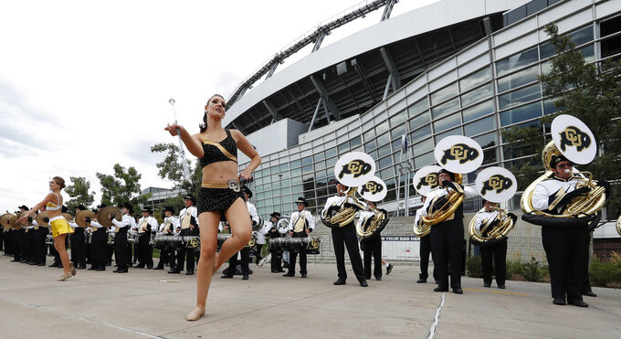 Baton-twirlers perform along with the Colorado marching band outside the stadium before Colorado faces Colorado State in an NCAA college football game Friday, Aug. 31, 2018, in Denver. (AP Photo/David Zalubowski)
