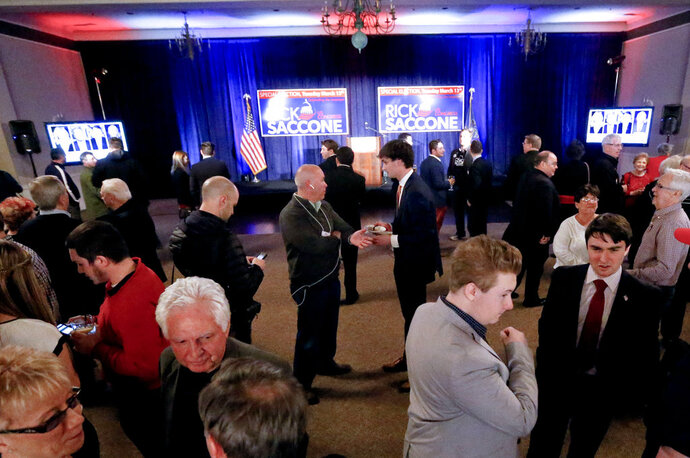 A crowd gathers in the ballroom of the Youghiogheny Country Club as they await returns for Republican Rick Saccone in the special election for the Pennsylvania 18th Congressional District seat vacated by Republican Tim Murphy, Tuesday, March 13, 2018, in McKeesport, Pa. Saccone is running against Democrat Conor Lamb. (AP Photo/Keith Srakocic)