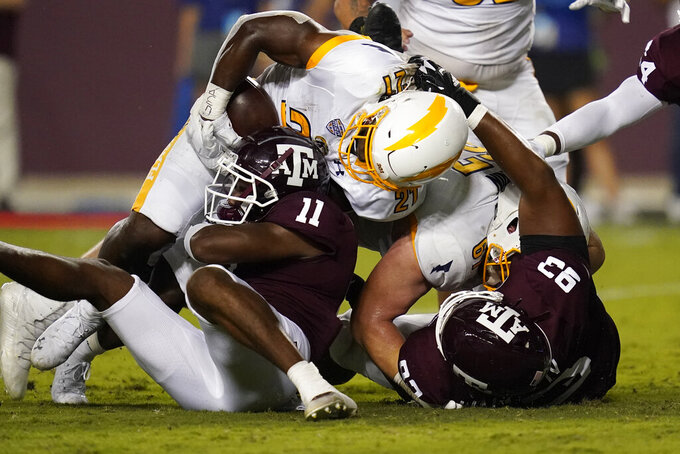 Kent State running back Joachim Bangda (21) is stopped short of the goal line by Texas A&M defensive back Deuce Harmon (11) and defensive lineman Dallas Walker IV (93) during the second half of an NCAA college football game on Saturday, Sept. 4, 2021, in College Station, Texas. (AP Photo/Sam Craft)