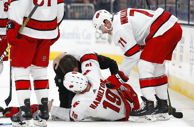 Carolina Hurricanes' head athletic trainer Doug Bennett attends to Dougie Hamilton after Hamilton was injured in the second period of an NHL hockey game against the Columbus Blue Jackets, Thursday, Jan. 16, 2020, in Columbus, Ohio. (AP Photo/Jay LaPrete)