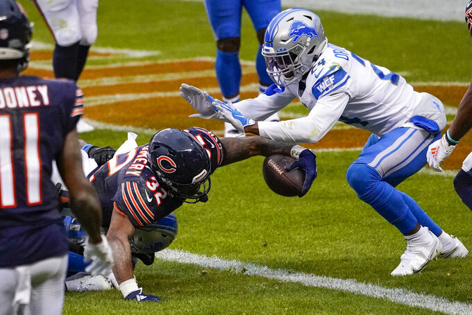 Chicago Bears running back David Montgomery (32) scores a touchdown under Detroit Lions cornerback Amani Oruwariye (24) in the first half of an NFL football game in Chicago, Sunday, Dec. 6, 2020. (AP Photo/Charles Rex Arbogast)