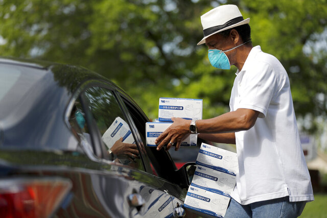 St. Louis area activist and pastor Rev. Darryl Gray hands boxes of face masks through an open car window to a church representative picking up protective equipment for their congregation, Thursday, May 28, 2020, in Hanley Hills, Mo. Gray is one of the organizers behind the effort to distribute about 150,000 masks to churches that plan to open as early as next week as restrictions surrounding the coronavirus outbreak ease. (AP Photo/Jeff Roberson)