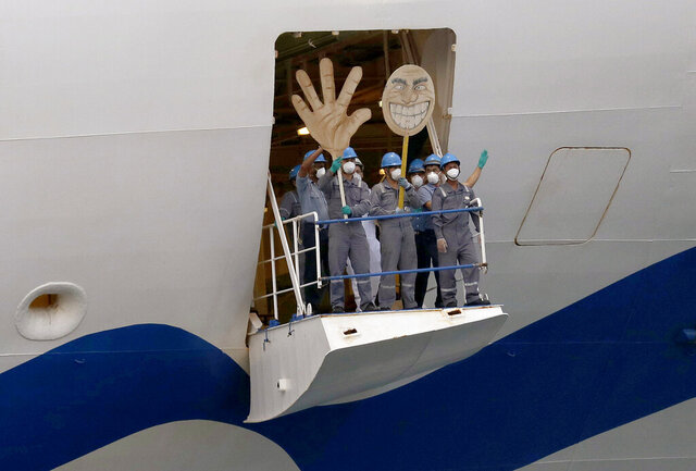 Crew on the the Ruby Princess wave with a cartoon sized hand and head as the ship departs from Port Kembla in Wollongong, Australia, Thursday, April 23, 2020. The ocean liner became notorious as Australia's largest single source of coronavirus infections and is the center of a criminal investigation over the sickness' spread set off a month after it was ordered by police to leave. (AP Photo/Rick Rycroft)