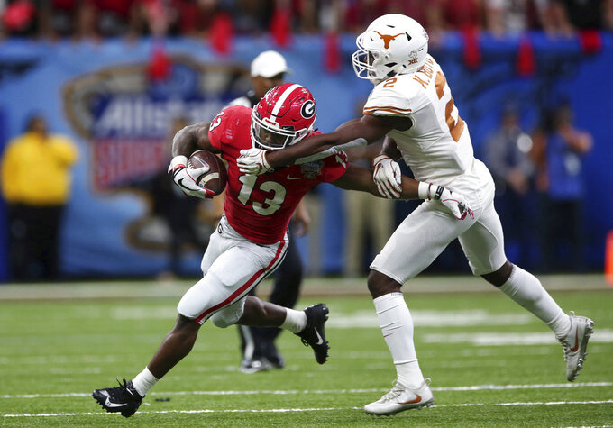 Georgia running back Elijah Holyfield (13) carries as Texas defensive back Kris Boyd (2) tries to make the tackle during the first half of the Sugar Bowl NCAA college football game in New Orleans, Tuesday, Jan. 1, 2019. (AP Photo/Rusty Costanza)