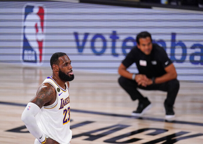 Los Angeles Lakers' LeBron James (23) looks on with Miami Heat's head coach Erik Spoelstra in the back ground during the first half in Game 3 of basketball's NBA Finals, Sunday, Oct. 4, 2020, in Lake Buena Vista, Fla. (AP Photo/Mark J. Terrill)