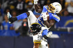 Los Angeles Chargers running back Melvin Gordon, top, is tripped up by Pittsburgh Steelers free safety Minkah Fitzpatrick as he runs the ball during the first half of an NFL football game, Sunday, Oct. 13, 2019, in Carson, Calif. (AP Photo/Kelvin Kuo)
