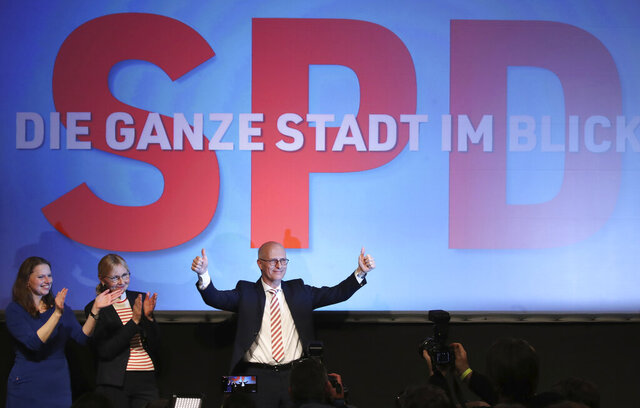 Social Democratic Party, SPD, top candidate and First Mayor of Hamburg Peter Tschentscher, right, celebrates with supporters after exit polls for the Hamburg state elections announced in Hamburg, Germany, Sunday, Feb. 23, 2020. Hamburg, Germany's second-biggest city which is also one of Germany's 16 federal states, elect a new regional assembly. Left are SAD member Melanie Leonhardlevt, and Peter Tschentscher wife Eva-Maria Peter Tschentscher, second from left. (Christian Charisius/dpa via AP)