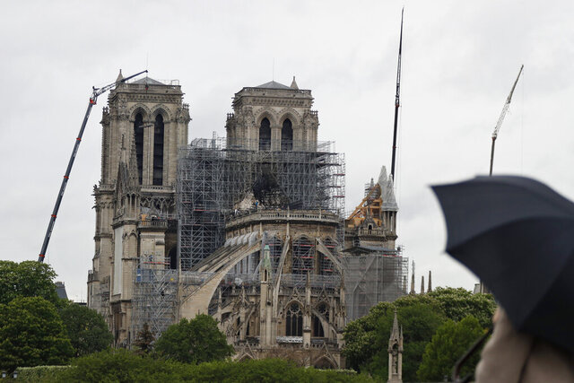 FILE - In this Thursday, April 25, 2019 file photo, cranes work at Notre Dame cathedral, in Paris. The body overseeing the Gothic structure's restoration issued a statement Sunday May 31, 2020, saying that the reopening to the public of the Notre Dame Cathedral's forecourt was finally made possible after several deep clean operations took place to remove toxic lead dust from the large forecourt. (AP Photo/Thibault Camus, File)
