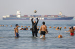 FILE - In this July 19, 2018 file photo, holidaymakers play in the Red Sea, at El Sokhna beach in Suez, Egypt, Egypt. The burkini, a swimsuit worn by conservative Muslims to cover the entire body, is scorned in many upper class Egyptian circles where it and the headscarf is seen as lower class. Women who wear the burkini or headscarves can face discrimination in upper-class beach resorts or in bars or clubs, though across Egypt the majority of women wear conservative dress. (AP Photo/Amr Nabil, File)