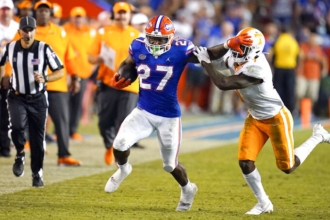 Florida running back Dameon Pierce (27) stiff-arms Tennessee defensive back Trevon Flowers, right, while running for yardage during the second half of an NCAA college football game, Saturday, Sept. 25, 2021, in Gainesville, Fla. (AP Photo/John Raoux)