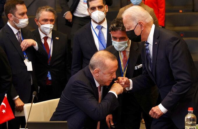 Turkey's President Recep Tayyip Erdogan, center, fist bumps with U.S. President Joe Biden, right, as he stands up to greet him during a plenary session at a NATO summit in Brussels, Monday, June 14, 2021. U.S. President Joe Biden is taking part in his first NATO summit, where the 30-nation alliance hopes to reaffirm its unity and discuss increasingly tense relations with China and Russia, as the organization pulls its troops out after 18 years in Afghanistan. (AP Photo/Olivier Matthys, Pool)