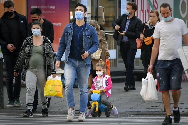 A girl wears a face mask for protection against COVID-19 infection while crossing a street in Bucharest, Tuesday, Oct. 20, 2020. Local authorities imposed the use of face masks in all public spaces, indoors and outdoors, closed schools, restaurants, theatres and cinemas after the rate of COVID-19 infections went above 3 cases per 1000 inhabitants in the Romanian capital Bucharest. (AP Photo/Andreea Alexandru)