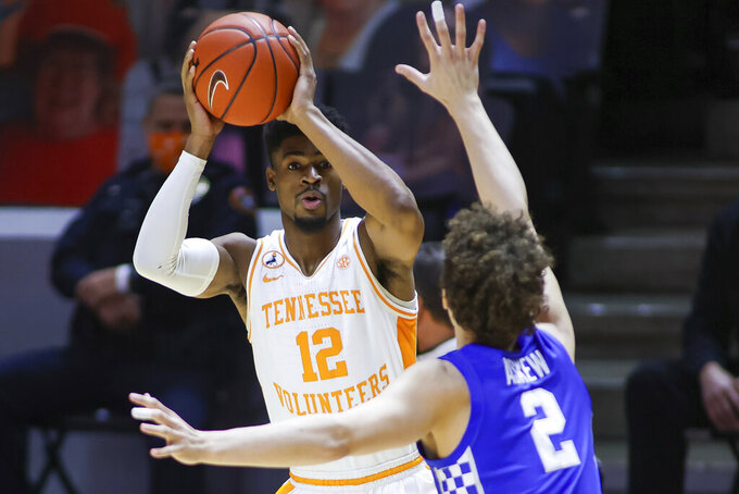 Tennessee guard Victor Bailey Jr. (12) looks to pass the ball against Kentucky's Devin Askew (2) during an NCAA college basketball game Saturday, Feb. 20, 2021, in Knoxville, Tenn. (Randy Sartin/Pool Photo via AP)