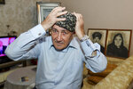 Velyeddin Ismayilov, 77, an Azerbaijani refugee from Kalbajar region puts on a national hat prior to his interview with the Associated Press in Baku, Azerbaijan, Wednesday, Nov. 25, 2020. Ismayilov says he fled Kalbajar with his wife and three young children, and his big house is now ruined. But he is prepared to return and restore his home town, and build a new house for his family.