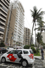 Police officers stand outside the beachfront apartment that sits at the center of the corruption case against former Brazilian President Luiz Inacio Lula da Silva, in Guaruja, Brazil, Monday, April 16, 2018. Members of a homeless movement occupied the beachfront apartment Monday. The 100 or so protesters left after four hours under a deal with police. Judges say the apartment in the city of Guaruja was promised to da Silva as a kickback from construction company OAS. (AP Photo/Andre Penner)
