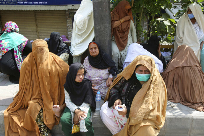 Women wait their turn outside a bank to receive cash under the government Ehsaas Emergency Cash Program for families in need, during a nationwide lockdown to try to contain the outbreak of the coronavirus, in Peshawar, Pakistan, Monday, June 29, 2020. (AP Photo/Muhammad Sajjad)