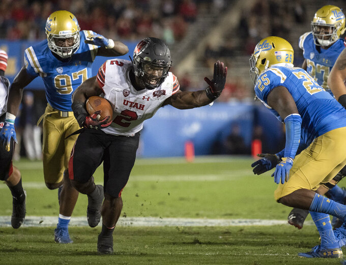 Utah running back Zack Moss, center, tries to sprint past UCLA linebacker Tyree Thompson, right, during the second half of an NCAA college football game Friday, Oct. 26, 2018, in Pasadena, Calif. (AP Photo/Kyusung Gong)