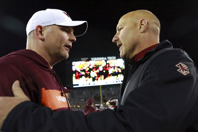 FILE - In this Nov. 3, 2018, file photo, Virginia Tech head coach Justin Fuente, left, meets with Boston College head coach Steve Addazio after an NCAA college football game in Blacksburg Va. Boston College won the game 31-21. Boston College won't have a chance to ease into its schedule this year. The Eagles open against Virginia Tech, just the second time in coach Steve Addazio's tenure that they have faced an Atlantic Coast Conference team in Week 1. Hokies coach Justin Fuente says BC is a tough opponent, no matter what week. (Matt Gentry/The Roanoke Times via AP, File)