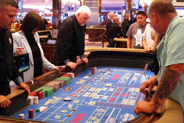 In this June 20, 2019 photo, players gather around a table for a game of craps at the Hard Rock casino in Atlantic City N.J. New Jersey's casinos won nearly $3.3 billion from gamblers in 2019, the first time since 2012 that the Atlantic City gambling halls had won more than $3 billion, according to figures released Tuesday, Jan. 14, 2020, by the New Jersey Division of Gaming Enforcement.  (AP Photo/Wayne Parry)