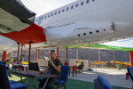 """Palestinians visit a Boeing 707 aircraft after it was converted to a cafe restaurant, in Wadi Al-Badhan, near the West Bank city of Nablus, Wednesday, Aug. 11, 2021. The Palestinian territory has no civilian airport and those who can afford a plane ticket must catch their flights in neighboring Jordan. After a quarter century of effort, twins brothers, Khamis al-Sairafi and Ata, opened the """"Palestinian-Jordanian Airline Restaurant and Coffee Shop al-Sairafi"""" on July 21, 2021, offering people an old airplane for customers to board. (AP Photo/Majdi Mohammed)"""