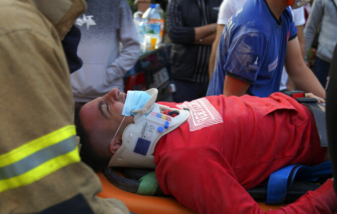 Rescuers carry a man rescued from the debris of his collapsed house, in Izmir, Turkey, Friday Oct. 30, 2020. A strong earthquake struck Friday in the Aegean Sea between the Turkish coast and the Greek island of Samos, killing several people and injuring hundreds amid collapsed buildings and flooding. (Ali Ihsan Mimtas/Depo Photos via AP)