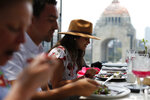 In this Aug. 26, 2019 photo, Jennifer Ramos, 28, visiting from Houston, Texas, eats chile en nogada with relatives at Arango restaurant in Mexico City. It can take hours to make one of the jewels of Mexican gastronomy, decorated in the green, white and red of the country's flag, and the sweet and salty dish is served only in the weeks around Mexico's independence celebrations. (AP Photo/Rebecca Blackwell)