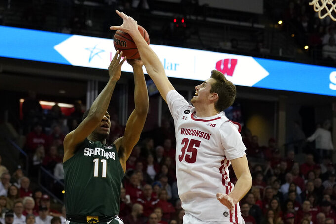 Wisconsin's Nate Reuvers (35) blocks a shot by Michigan State's Aaron Henry (11) during the first half of an NCAA college basketball game Saturday, Feb. 1, 2020, in Madison, Wis. (AP Photo/Andy Manis)