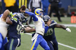 Los Angeles Rams quarterback Jared Goff passes as Seattle Seahawks defensive tackle Jarran Reed, right, pressures him during the first half of an NFL wild-card playoff football game, Saturday, Jan. 9, 2021, in Seattle. (AP Photo/Scott Eklund)