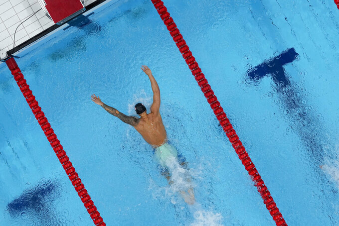 Caeleb Dressel, of the United States, swims to victory in a men's 100m butterfly semifinal at the 2020 Summer Olympics, Friday, July 30, 2021, in Tokyo, Japan. (AP Photo/Jeff Roberson)