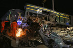 Railway workers try to clear the track at the site of a train collision in the Ghotki district, southern Pakistan, late Monday, June 7, 2021. An express train barreled into another that had derailed in Pakistan before dawn Monday, killing dozens of passengers, authorities said. More than 100 were injured, and rescuers and villagers worked throughout the day to search crumpled cars for survivors and the dead. (AP Photo/Fareed Khan)