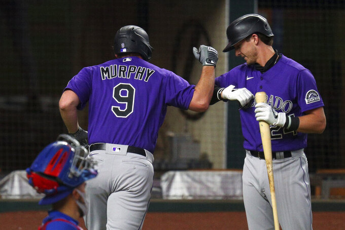 Colorado Rockies Daniel Murphy (9) bumps elbows with Ryan McMahon (24) after a solo home run against the Texas Rangers in an exhibition baseball game Tuesday, July 21, 2020 in Arlington, Texas. (AP Photo/Richard W. Rodriguez)