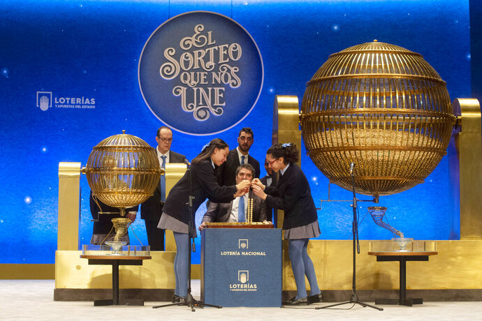 Children from Madrid's San Ildefonso school pick out lottery ticket numbers at Madrid's Teatro Real opera house during Spain's bumper Christmas lottery draw in Madrid, Spain, Sunday, Dec. 22, 2019. The lottery, known as El Gordo, or The Fat One, will dish out 2.24 billion euros ($2.43 billion) in prizes. (AP Photo/Paul White)