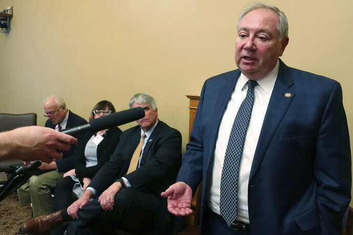 In this photo from Tuesday, Feb. 4, 2020, Kansas Senate Majority Leader Jim Denning, R-Overland Park, answers questions from reporters about Medicaid expansion following a news conference with other backers of a bipartisan plan at the Statehouse in Topeka, Kan. Denning is urging lawmakers not to add a work requirement to the expansion legislation. (AP Photo/John Hanna)