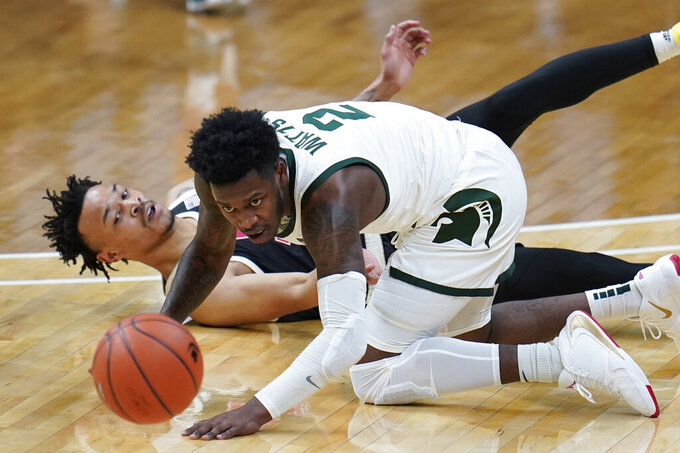 Nebraska guard Trey McGowens (2) knocks the ball from Michigan State guard Rocket Watts (2) in the first half of an NCAA college basketball game in East Lansing, Mich., Saturday, Feb. 6, 2021. (AP Photo/Paul Sancya)