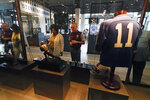 Guests look at memorabilia including the Heisman Trophy at Steve Spurrier's Gridiron Grill, Thursday, June 17, 2021, in Gainesville, Fla. The restaurant doubles as Spurrier's personal museum. (AP Photo/John Raoux)