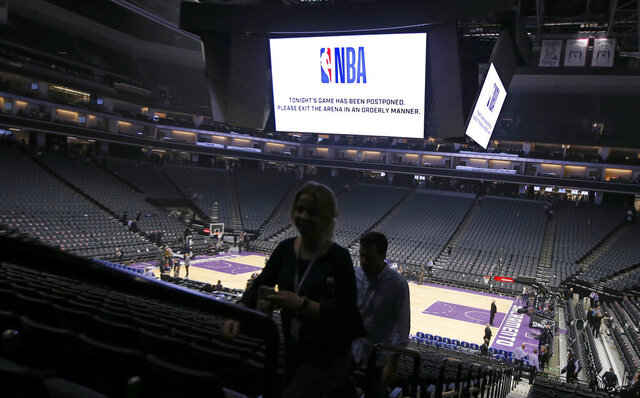 Fans leave the Golden 1 Center after the NBA basketball game between the New Orleans Pelicans and Sacramento Kings was postponed at the last minute in Sacramento, Calif., Wednesday, March 11, 2020. The league said the decision was made out of an