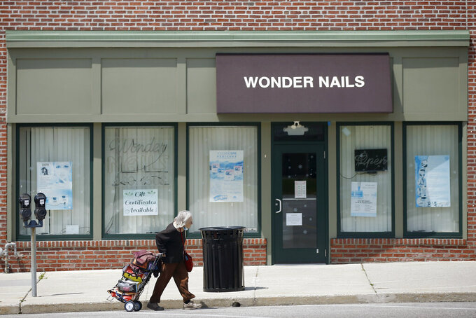 A person walks past a row of closed businesses, Wednesday, April 29, 2020, in Upper Darby, Pa. Devastated by the coronavirus, the U.S. economy is sinking.  Now, as some businesses in a few states start to trickle back to work, hopes are beginning to arise that the economy, damaged as it is, might be poised to rebound by the second half of the year.  (AP Photo/Matt Slocum)