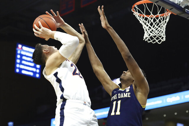 Virginia center Francisco Caffaro (22) goes up with the ball as Notre Dame's Juwan Durham (11) defends during an NCAA college basketball game  Wednesday, Jan. 13, 2021, in Charlottesville, Va. (Erin Edgerton/The Daily Progress via AP, Pool)