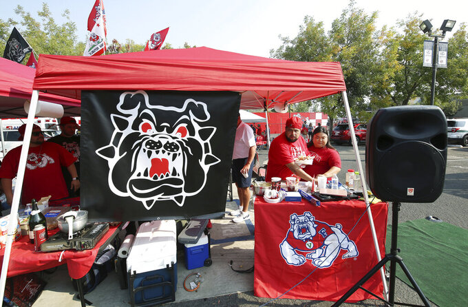 Jordan Salazar and Junny Saechao eat at a tailgate party before the Connecticut at Fresno State NCAA college football game in Fresno, Calif., Saturday, Aug. 28, 2021. Colleges across the country are cautiously optimistic that pregame tailgating atmospheres around campus will remain close to normal even as they monitor how things have changed since the emergence of the delta variant. (AP Photo/Gary Kazanjian)