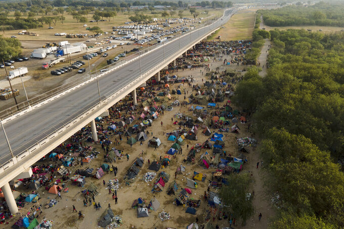 Migrants, many from Haiti, are seen at an encampment along the Del Rio International Bridge near the Rio Grande, Tuesday, Sept. 21, 2021, in Del Rio, Texas.  The options remaining for thousands of Haitian migrants straddling the Mexico-Texas border are narrowing as the United States government ramps up to an expected six expulsion flights to Haiti and Mexico began busing some away from the border.  (AP Photo/Julio Cortez)