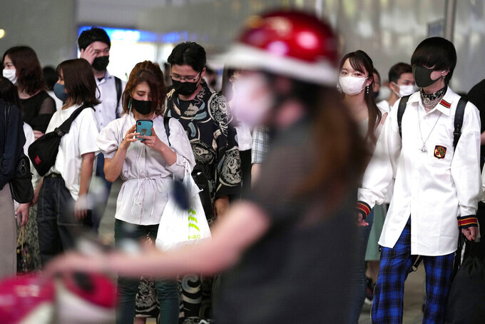 People wait for a traffic light at a pedestrian crossing Friday, July 30, 2021, in Tokyo, as Japanese Prime Minister Yoshihide Suga expanded a coronavirus state of emergency to four more areas in addition to Tokyo following record spikes in infections as the capital hosts the Olympics. (AP Photo/Eugene Hoshiko)