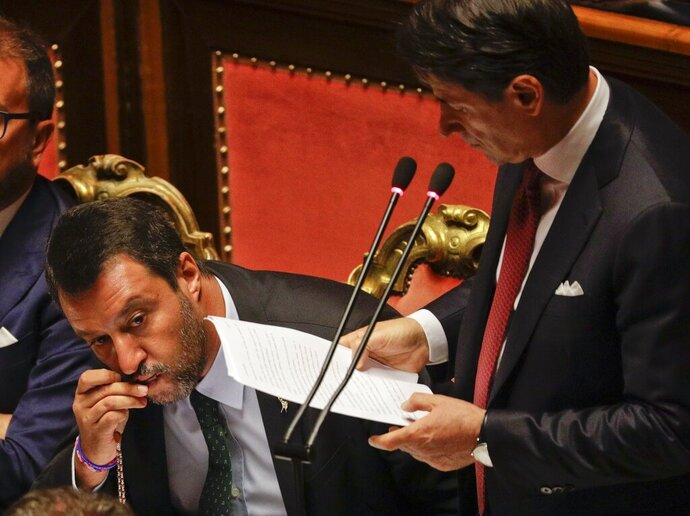 Italian Premier Giuseppe Conte addresses the Senate as Deputy-Premier Matteo Salvini kisses a rosary while sitting beside him, in Rome, Tuesday, Aug. 20, 2019. Italian Premier Conte blasted the League's leader Salvini for his decision to spark a government crisis that risks triggering
