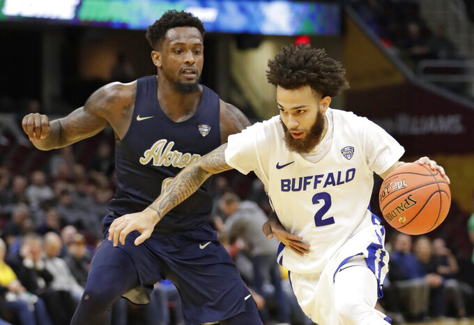 Buffalo's Jeremy Harris (2) drives past Akron's Jimond Ivey (0) during the first half of an NCAA college basketball game at the Mid-American Conference tournament, Thursday, March 14, 2019, in Cleveland. (AP Photo/Tony Dejak)