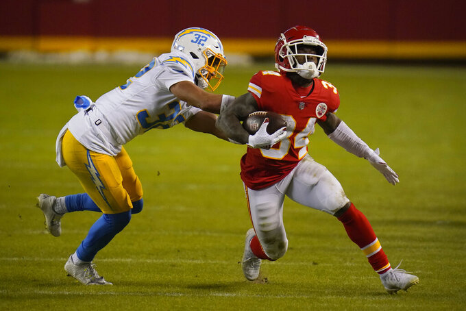 Kansas City Chiefs running back Darwin Thompson (34) runs from Los Angeles Chargers safety Alohi Gilman (32) during the second half of an NFL football game, Sunday, Jan. 3, 2021, in Kansas City. (AP Photo/Jeff Roberson)