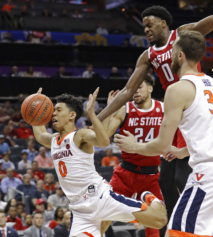 Virginia's Kihei Clark (0) loses the ball as he drives between North Carolina State's Devon Daniels (24) and DJ Funderburk, back, during the first half of an NCAA college basketball game in the Atlantic Coast Conference tournament in Charlotte, N.C., Thursday, March 14, 2019. (AP Photo/Chuck Burton)