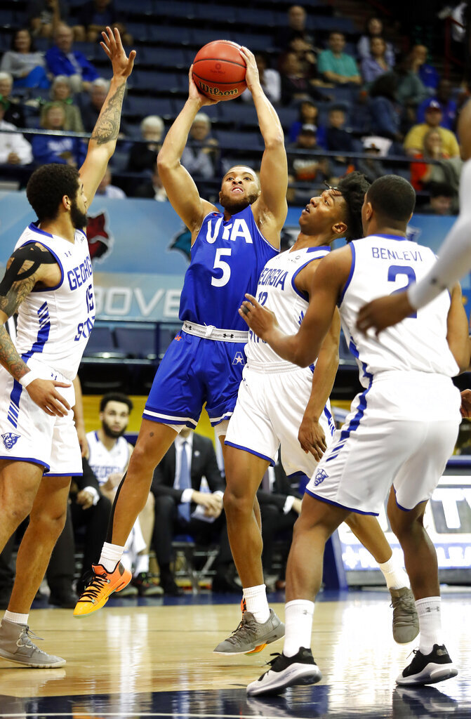 Texas-Arlington guard Edric Dennis (5) is defended by Georgia State guard D'Marcus Simonds (15) and guard Kane Williams (12) during the first half of the NCAA college basketball championship game of the Sun Belt Conference men's tournament in in New Orleans, Sunday, March 17, 2019. (AP Photo/Tyler Kaufman)