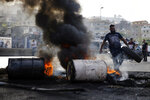An anti-government protester burns tires to close the main highways during ongoing protests against the government, in Khaldeh, south of Beirut, Lebanon, Thursday, Nov. 14, 2019. Protesters have been holding demonstrations since Oct. 17 demanding an end to widespread corruption and mismanagement by the political class that has ruled the country for three decades. (AP Photo/Bilal Hussein)
